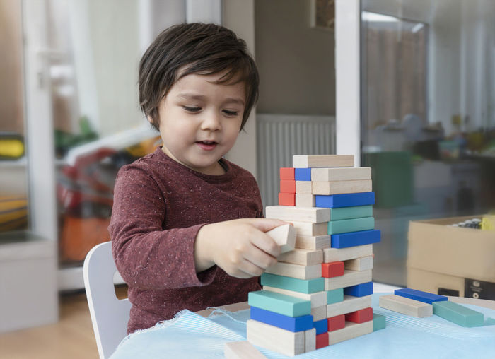 Close-up of cute boy playing with wooden blocks on table