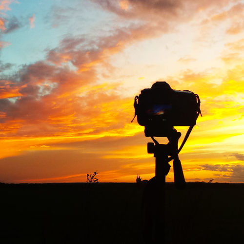 Tripod Camera On Silhouette Field Against Sky During Sunset