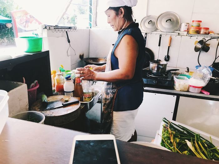 Side view of woman standing in kitchen at home