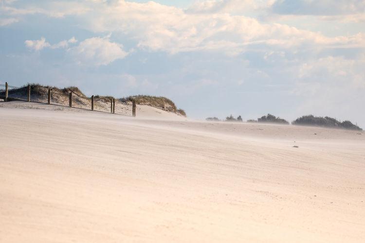 Panoramic view of sand dunes in desert against sky