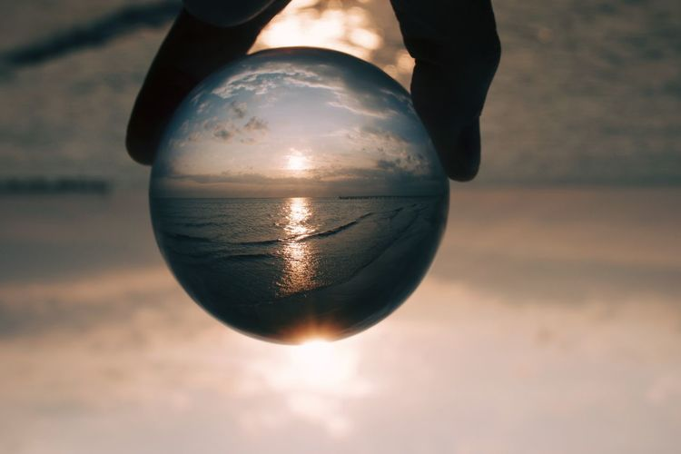 Midsection of person holding crystal ball against sky during sunrise