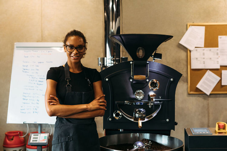 Portrait Of Female Owner Standing By Coffee Grinder In Cafe