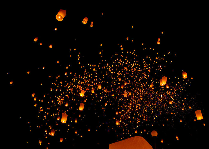 Low angle view of lanterns flying against sky at night