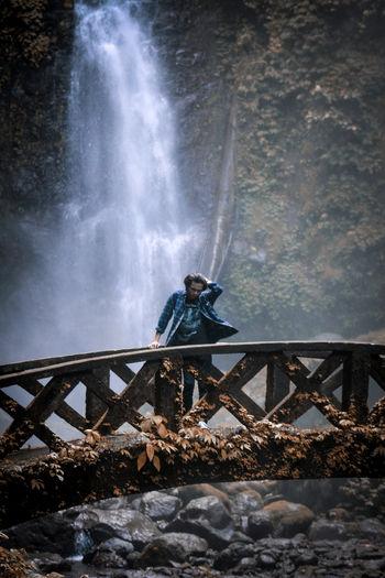 Man standing on footbridge against waterfall in forest