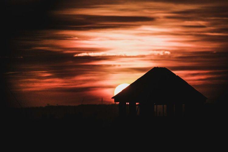 Silhouette house against orange sky at sunset