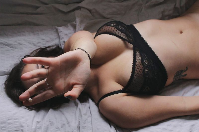 High angle view of sensual woman on bed