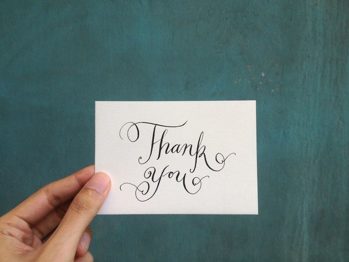 Close-up of hand holding paper with thank you text against wall
