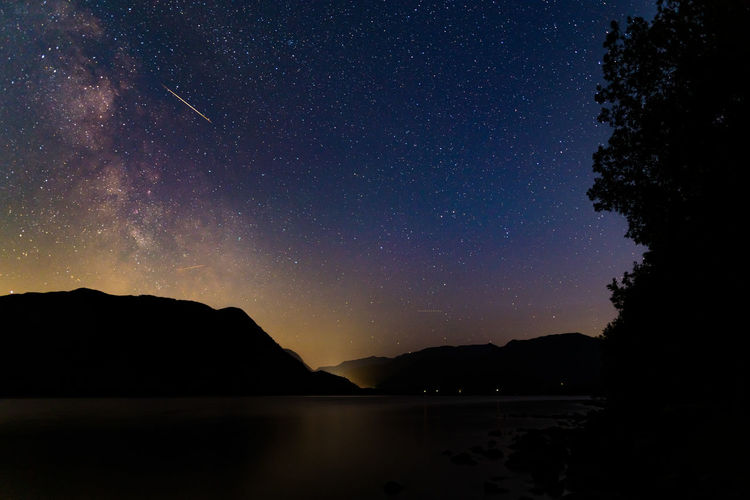 The milky way over ullswater in the english lake district with a meteorite flashing across the sky