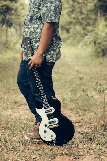 Man holding guitar on field