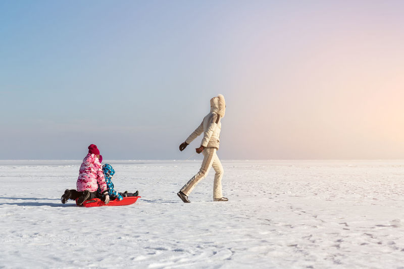 People on snow covered land against clear sky