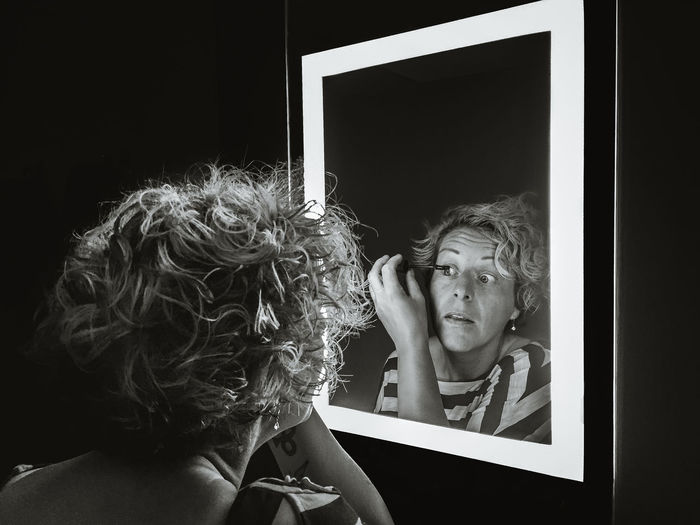 Reflection of woman in mirror while applying mascara