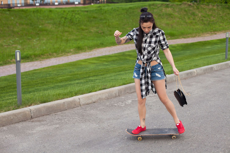 On the background of green grass the woman with bag in pink shoes is skating. Adolescence  Teenager Outdoors Riding Childhood Nature Men Shorts Transportation Motion Road Plant Lifestyles Day Child Grass Sports Equipment Skateboard Casual Clothing Leisure Activity Sport One Person Full Length Real People Boys