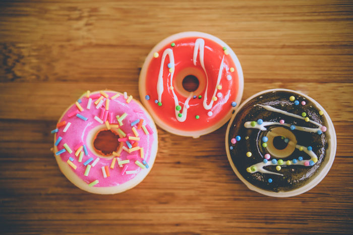Table Indoors  Wood - Material Still Life Food And Drink Donut Sweet Food No People Food Directly Above Sweet Circle Indulgence Geometric Shape Focus On Foreground Baked Close-up Multi Colored Pink Color Shape Temptation Crockery Snack