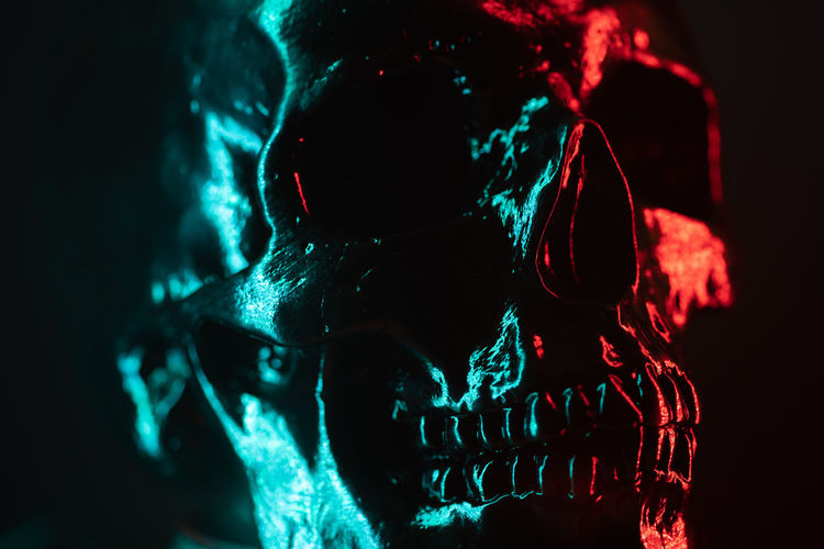 Ancient human skull head close-up. Neon turquoise and red light. Spooky and sinister. Glamour, disco, halloween concept. Indoors  Illuminated One Person Close-up Studio Shot Human Body Part Dark Body Part Front View Black Background Adult Arts Culture And Entertainment Headshot Technology Glowing Red Green Color Leisure Activity Standing Nightlife