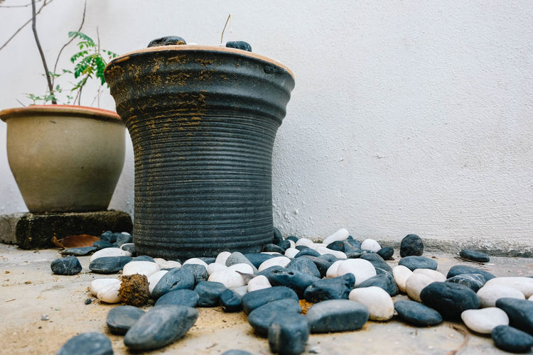 ceramic vase and black stone at garage Abundance Architecture Built Structure Day Geometric Shape Heap Large Group Of Objects Man Made Object No People Pebble Rock - Object Shore Stone Stone - Object Stone Material Surface Level Wall - Building Feature