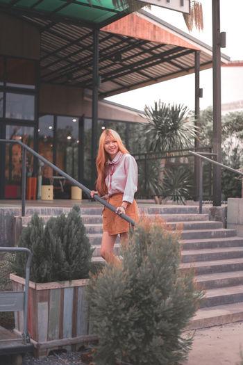 Portrait of happy woman standing against plants