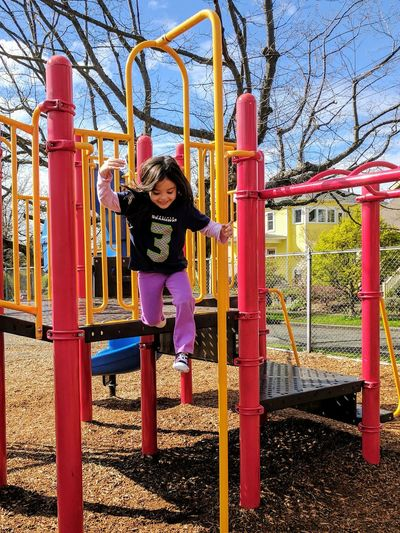 Full length of girl playing on swing in park