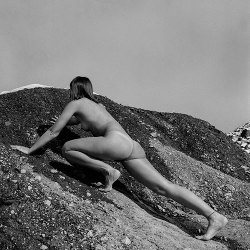 Naked woman crawling on rock against sky