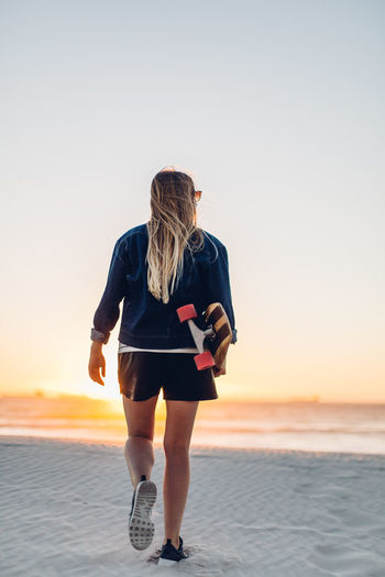 Rear view of young woman with skateboard walking at beach against clear sky during sunset