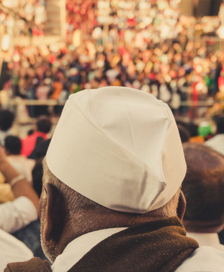 Close up of an old indian man wearing a cap at the stadium amidst the crowd