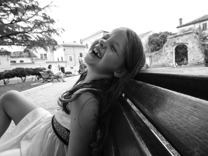 Girl Laughing While Sitting Outdoors