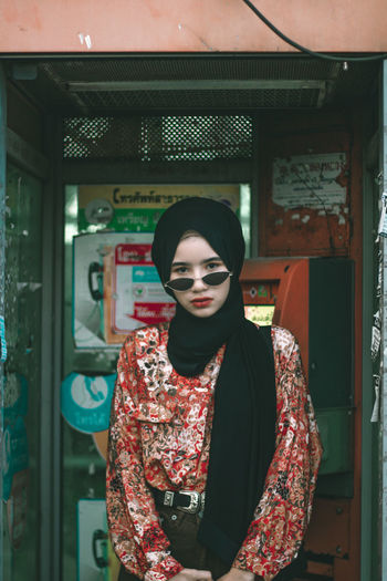 Portrait of girl standing in telephone booth