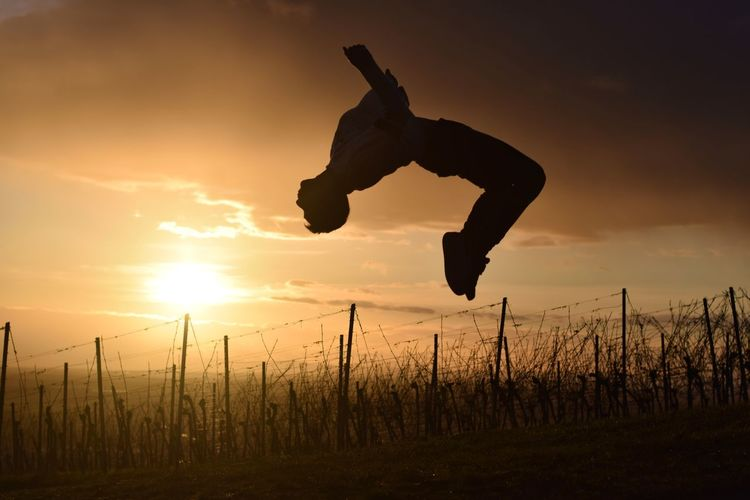 Silhouette man jumping on field against sky during sunset