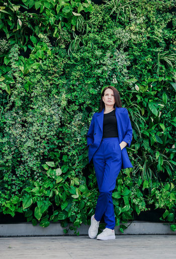 Full length of woman standing against plants