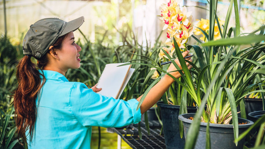 Female researcher examining flowers in greenhouse