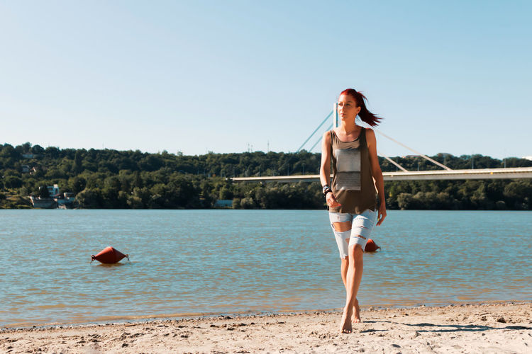 Full length of redhead woman walking on the sand at the beach. copy space.