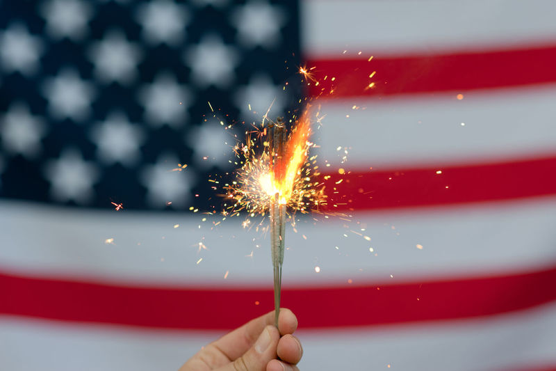 USA flag Celebration One Person Firework Holding Sparkler Sparks Human Hand Motion Red Burning Real People Illuminated Hand Firework - Man Made Object Event Human Body Part Blurred Motion Glowing Long Exposure Firework Display Outdoors Finger
