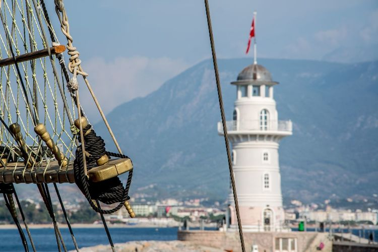 Lighthouse at shore with ropes in foreground