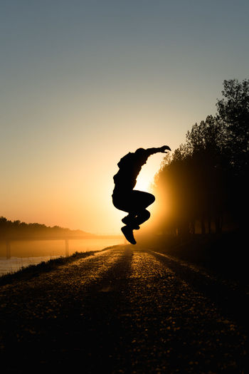 Silhouette man jumping on tree against sky during sunset