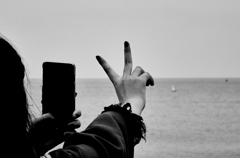Close-up of woman photographing while gesturing peace sign at beach