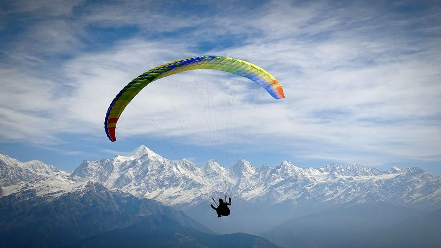 Silhouette Man Paragliding By Snow Covered Mountains Against Sky