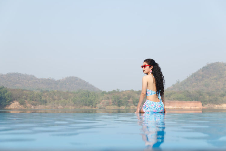 Young Woman Standing At Infinity Pool Against Clear Sky