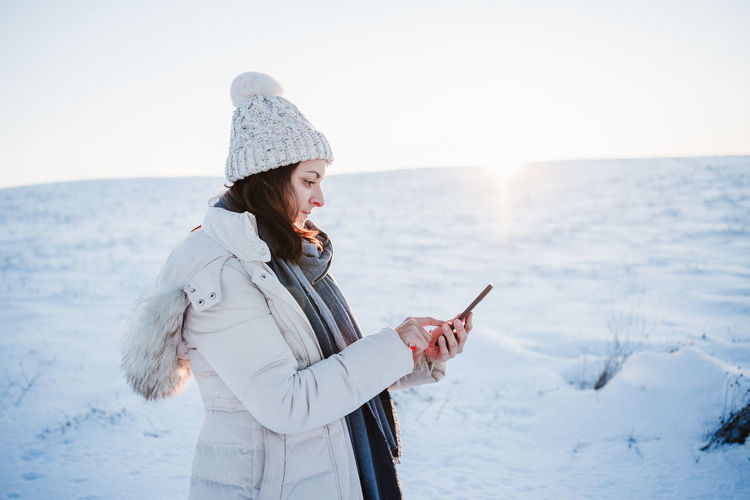 Side view of woman using mobile phone while standing on snow covered land