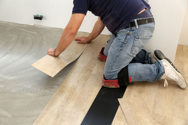 Low section of carpenter installing laminate on floor