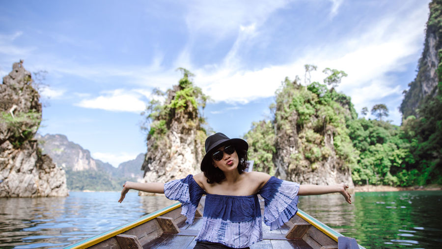 Portrait of young woman pouting while sitting on boat in sea against rock formations and sky