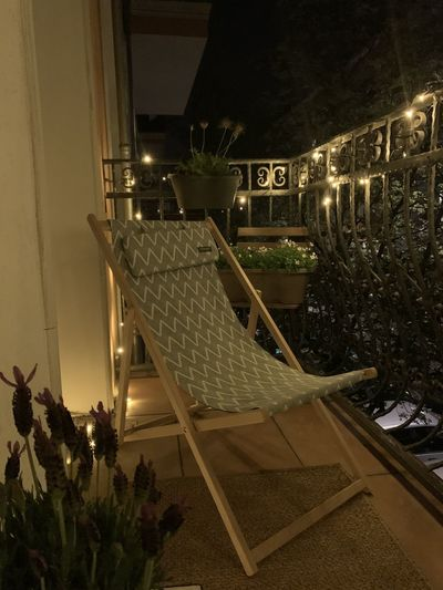 Chairs and tables by illuminated railing at night