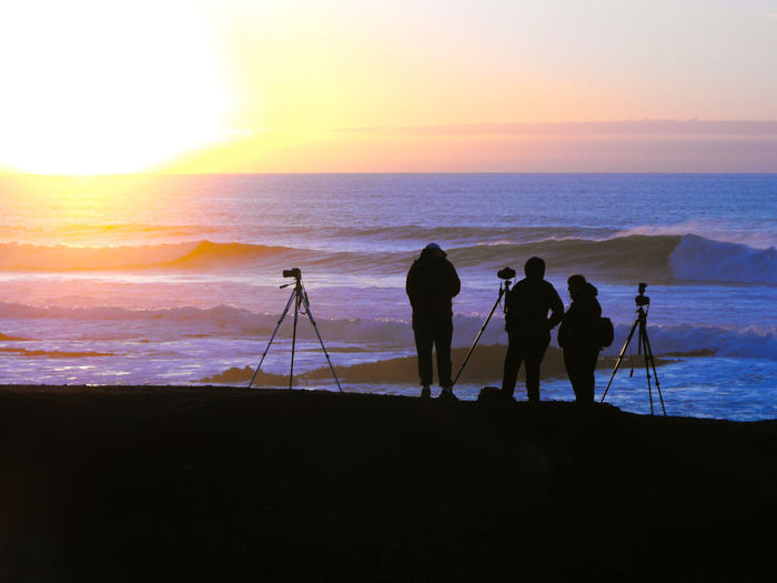 Silhouette people photographing at beach during sunset