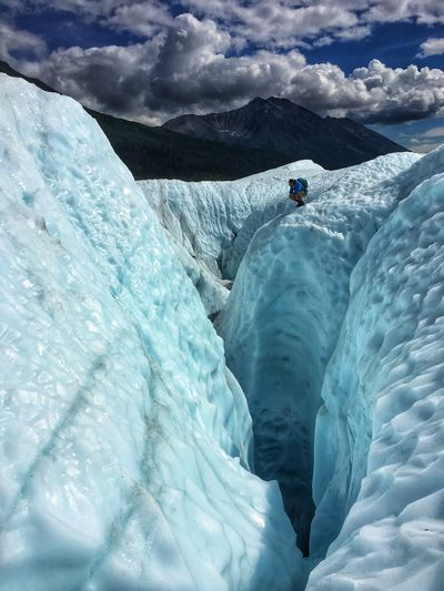 Distant view of man crouching by cracks in glaciers