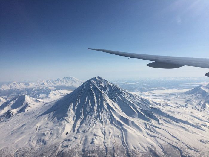 Cropped image of aircraft wing over snow covered mountains against sky