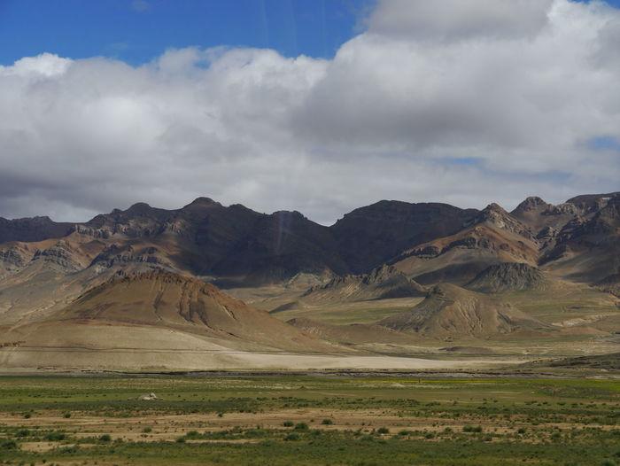 Countryside Landscape Against Mountain Range