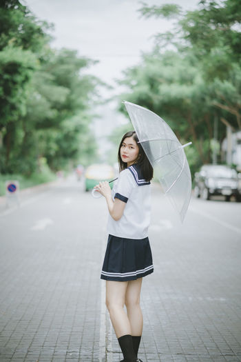 Portrait of young woman with umbrella standing on road