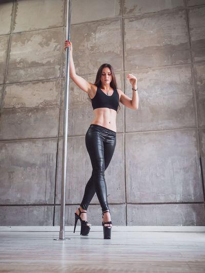 Full length of sensuous woman practicing pole dance in studio