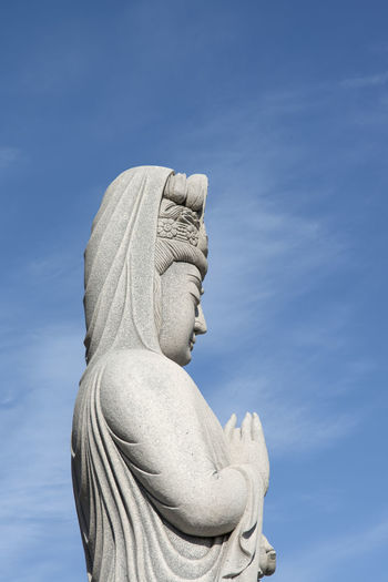 Buddha statue at Yongmunsa, a Buddhism temple in Jeju Island, South Korea Blue Buddha Buddhsim Close-up Cloud - Sky Day Human Representation Low Angle View No People Outdoors Religion Religion And Beliefs Religion And Tradition Sculpture Sky Spirituality Statue Yongmunsa