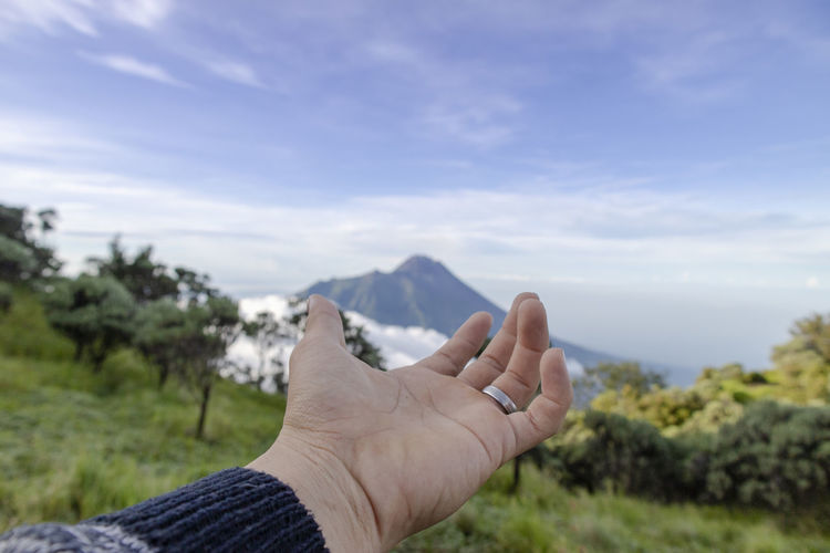 Cropped hand of person against landscape