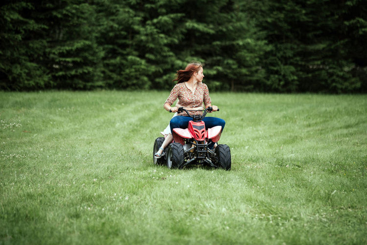Family riding with kids atv and having fun on grass. Fun Funny Day Riding Roller Coasters Adult Atv Bonding Childhood Day Enjoying Life Family With One Child Grass Nature Outdoors People Riding Togetherness Young Adult EyeEmNewHere EyeEm Ready   Love Yourself