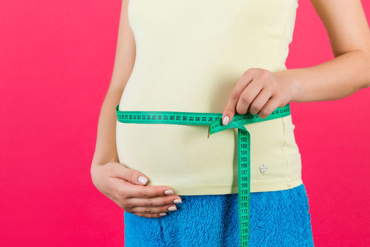Midsection of woman holding pink while standing against colored background
